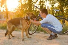 有一条德国牧羊犬狗的愉快的人在公园 免版税库存图片