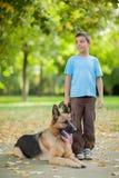 有一条德国牧羊犬狗的愉快的孩子在公园 图库摄影