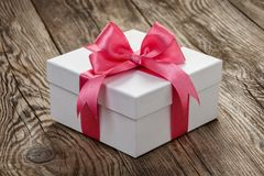 有一条桃红色丝带的白色礼物盒在老委员会 图库摄影