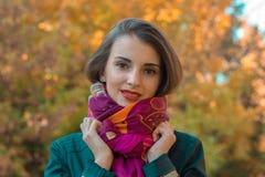 有一条桃红色围巾的逗人喜爱的女孩在秋天街道上站立 免版税库存图片