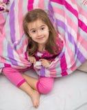 有一条毯子的一个小女孩在床上 库存图片