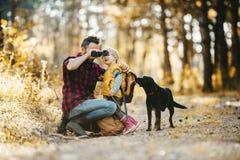 有一条狗和一个小孩儿子的一个成熟父亲在秋天森林里,使用双筒望远镜 库存照片