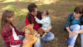 有一条狗和孩子的幸福家庭一次野营的 有他们的父亲的无忧无虑的少年在一个休息日 ?? 股票录像