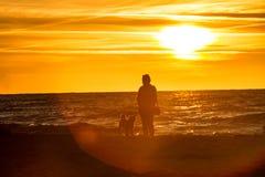 有一条狗的一个人在日落 免版税库存图片