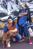 有一条狗的两位斥责歌手在有街道画的一个地铁在后面 免版税库存图片