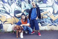 有一条狗的两位斥责歌手在有街道画的一个地铁在后面 库存图片