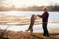 有一条狗的人在河的河岸 免版税库存图片