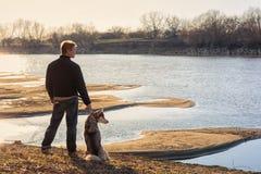 有一条狗的人在河的河岸 免版税库存照片