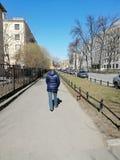 有一条狗的夫人在城市附近的步行 库存照片
