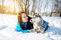 有一条狗的女孩在冬天爱斯基摩 免版税库存照片