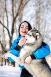 有一条狗的女孩在冬天爱斯基摩 库存图片
