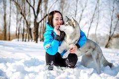 有一条狗的女孩在冬天爱斯基摩 免版税库存图片
