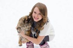 有一条狗的女孩在她的胳膊 免版税库存照片