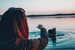 有一条狗的女孩在湖 库存图片