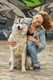 有一条狗的女孩在街道上 免版税库存图片