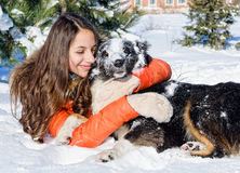 有一条狗的女孩在雪 免版税库存图片
