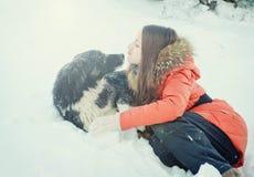 有一条狗的女孩在雪 免版税库存照片