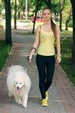 有一条狗的女孩步行的 免版税库存图片