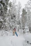 有一条狗的妇女在冬天木头的步行 库存图片