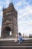 有一条狗的妇女在查理大桥前面塔  免版税库存图片