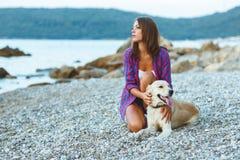 有一条狗的妇女在海滩的步行 图库摄影