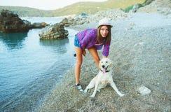 有一条狗的妇女在海滩的步行 免版税图库摄影