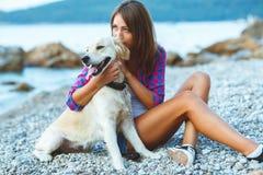 有一条狗的妇女在海滩的步行 库存照片