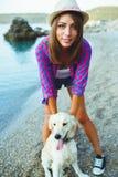 有一条狗的妇女在海滩的步行 库存图片