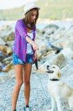 有一条狗的妇女在海滩的步行 免版税库存照片