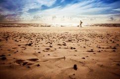 有一条狗的妇女在海滩 免版税库存图片