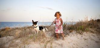 有一条狗的小女孩在海滩 库存照片