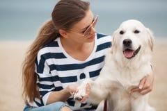 有一条狗的少妇在一个离开的海滩 库存图片