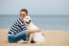 有一条狗的少妇在一个离开的海滩 库存照片