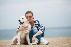 有一条狗的少妇在一个离开的海滩 免版税库存图片
