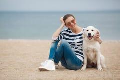 有一条狗的少妇在一个离开的海滩 免版税图库摄影