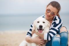 有一条狗的少妇在一个离开的海滩 图库摄影