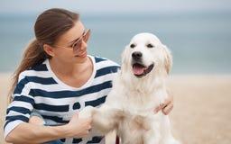 有一条狗的少妇在一个离开的海滩 免版税库存照片