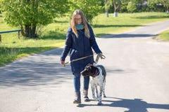有一条狗的美丽的女孩在步行 免版税库存照片