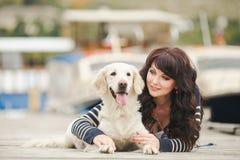 有一条狗的美丽的女孩在码头在夏天 免版税图库摄影