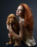 有一条狗的美丽的红发女孩在黑暗 免版税库存图片