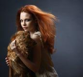 有一条狗的美丽的红发女孩在黑暗 免版税库存照片