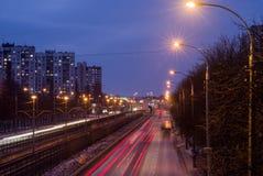 有一条电车线的城市高速公路在晚上 免版税库存图片