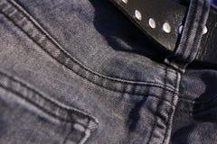 有一条皮带的灰色牛仔裤 免版税图库摄影