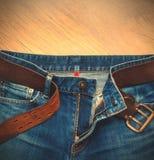 有一条皮带的年迈的蓝色牛仔裤 免版税库存照片
