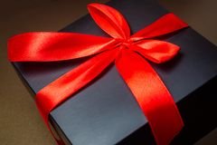 有一条红色丝带的在金背景的黑匣子和弓 Abstra 免版税图库摄影