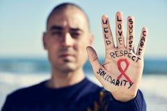 有一条红色丝带的年轻人与艾滋病的战斗的在他的ha 免版税库存照片
