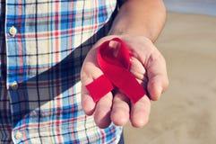有一条红色丝带的年轻人与艾滋病的战斗的,被过滤 免版税库存照片