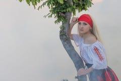 有一条红色围巾、一件传统罗马尼亚女衬衫和一条红色和黑裙子的美丽的年轻白肤金发的女孩 库存图片