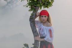 有一条红色围巾、一件传统罗马尼亚女衬衫和一条红色和黑裙子的美丽的年轻白肤金发的女孩 库存照片