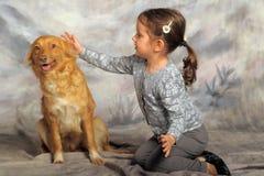 有一条红色狗的小女孩 库存照片